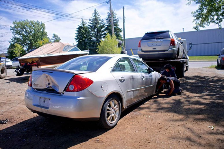 two people recycling a car in scrapyard